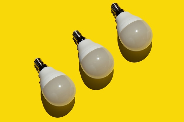 Três lâmpadas economizadoras de energia em um fundo amarelo