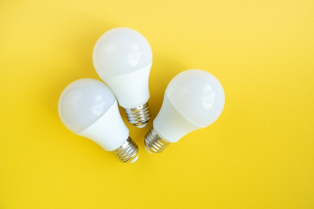 Três lâmpadas led em fundo amarelo. conceito de economia de energia.