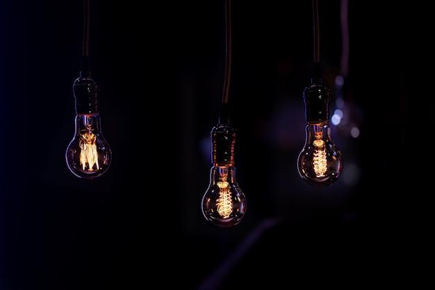 Três lâmpadas luminosas penduradas no escuro da boke. conceito de decoração e ambiente.