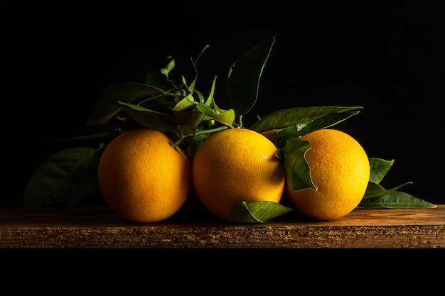 Três laranjas com folhas em uma mesa de madeira em um fundo escuro