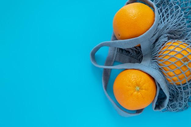 Três laranjas maduras estão em uma sacola ecológica cinza-azulada sobre fundo azul