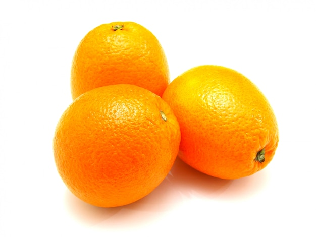Três laranjas maduras ficam nas proximidades