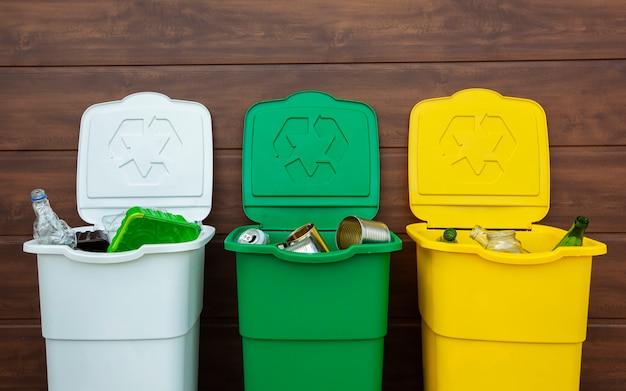 Três latas de lixo cheias para separar o lixo no quintal