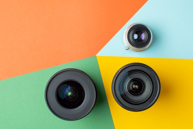 Três lentes fotográficas em um fundo colorido