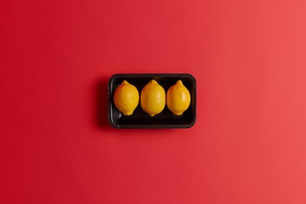 Três limões deliciosos azedos amarelos inteiros na bandeja preta isolada sobre o fundo vermelho do estúdio. produtos naturais ricos em vitamina c. conceito de nutrição saudável. frutas cítricas frescas orgânicas. vista do topo