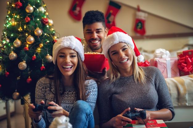 Três lindas amigas brincalhões curtindo videogame e pipoca em casa nas férias de natal.