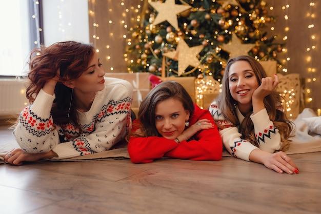 Três lindas garotas deitam-se perto da árvore de natal à espera de presentes. melhores amigas da jovem comemorando o natal em casa. lindas decorações douradas de natal em uma alta árvore de natal