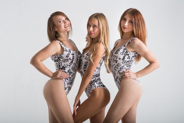 Três lindas garotas em maiôs em um fundo cinza