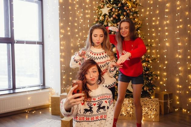 Três lindas garotas fazem selfie no telefone, careta. melhores amigas da jovem comemorando o natal em casa. lindas decorações douradas de natal em uma alta árvore de natal