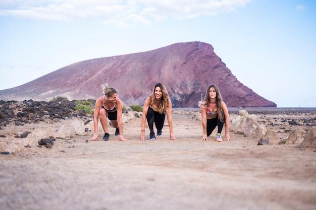 Três lindas garotas jovens se preparando e prontas para começar a correr para atividades de lazer ao ar livre, esporte e corpo. mantenha-se saudável fazendo exercícios e fitness. montanha d