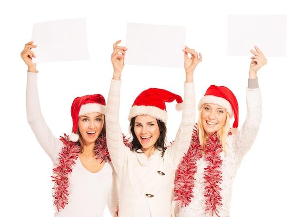 Três lindas garotas na véspera de ano novo em pé com folhas de papel em branco