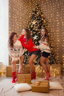 Três lindas garotas na véspera de ano novo. melhores amigas da jovem comemorando o natal em casa. prazer amizade nunca termina o conceito. lindas decorações douradas de natal em uma alta árvore de natal