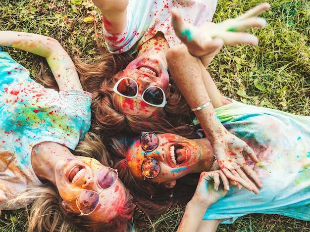 Três lindas garotas sorridentes posando na festa holi