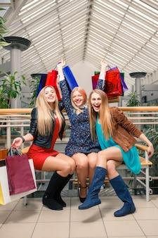 Três lindas meninas com sacolas de compras