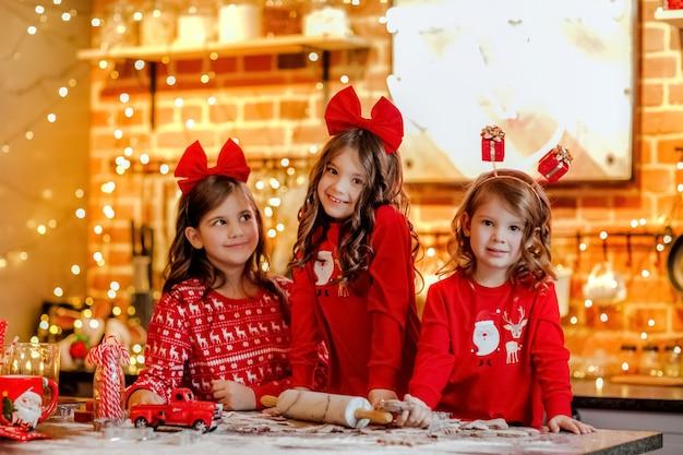 Três lindas meninas de pijama vermelho de natal e bandanas fazendo biscoitos na cozinha com fundo de natal.