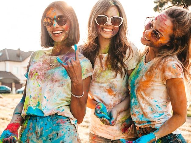 Três lindas meninas felizes fazendo festa no festival de cores de holi