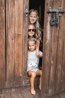 Três lindas meninas irmãs brincando juntos no celeiro de madeira