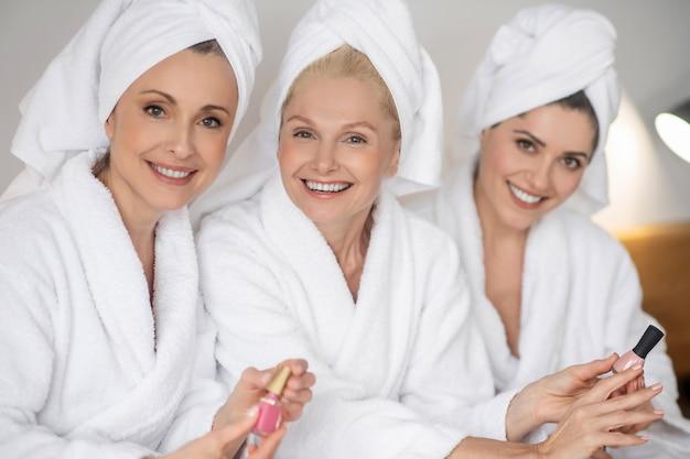 Três lindas mulheres pegando esmalte