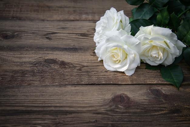 Três lindas rosas brancas em um fundo de madeira rústico, copie o espaço
