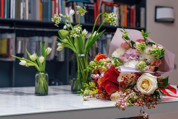 Três lindos buquês de primavera arranjos de flores com várias cores em um vaso de vidro na mesa