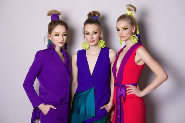Três lindos modelos de moda com maquiagem colorida e roupas de grife
