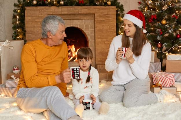 Três lindos parentes em casa, adorável garota encantadora com a mãe e o avô