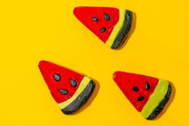 Três lindos pirulitos coloridos parecem uma melancia em um fundo amarelo