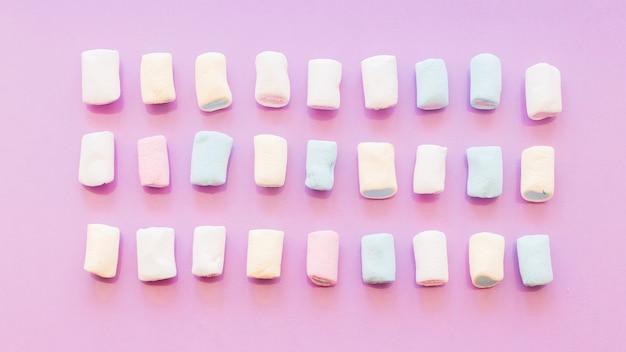 Três linhas de marshmallow no fundo rosa