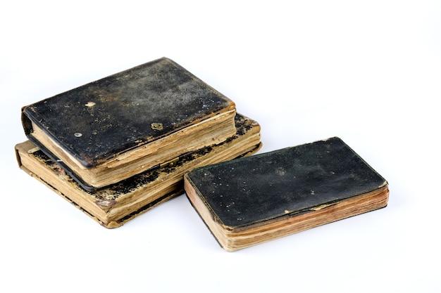 Três livros antigos isolados sobre uma mesa branca