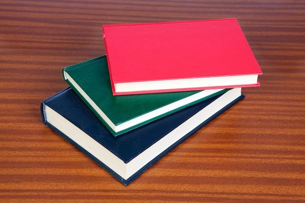 Três livros de capa dura em uma superfície de madeira