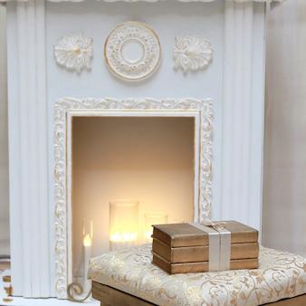 Três livros dourados no pufe perto da lareira
