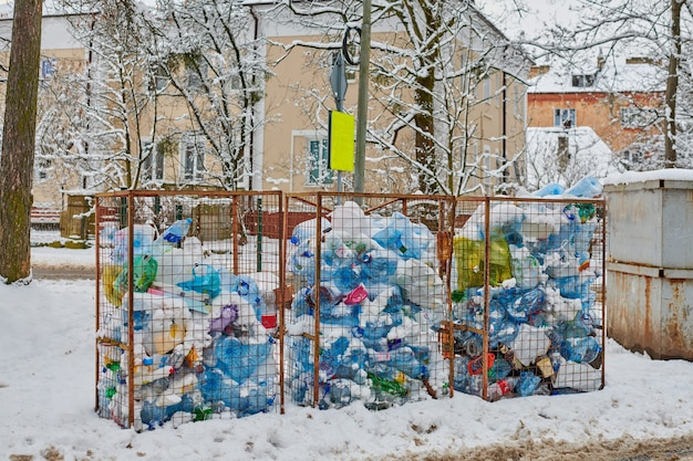 Três lixeiras abertas cheias de garrafas e sacos plásticos. resíduos de plástico em grandes latas de lixo