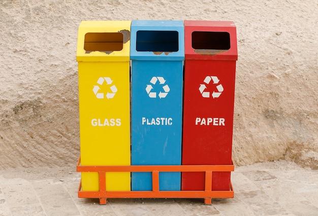 Três lixeiras coloridas, com sinais de envelhecimento e ferrugem, para a coleta seletiva - protegendo o meio ambiente