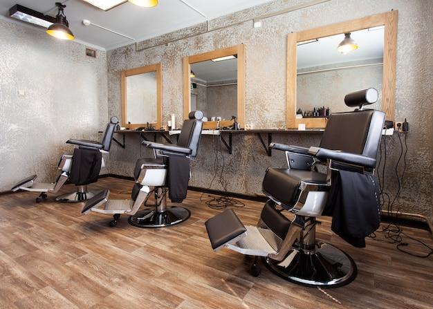 Três locais de trabalho para barbeiros, poltronas e espelhos