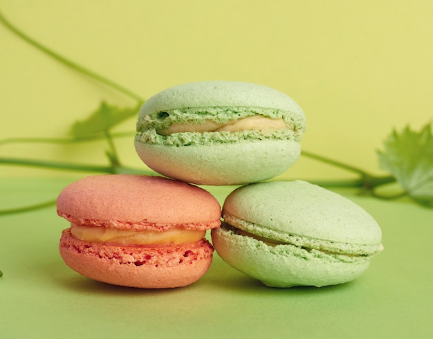 Três macarons assados multicoloridos redondos, a sobremesa fica uma em cima da outra em um verde