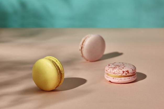 Três macarons em um fundo rosa claro e azul claro