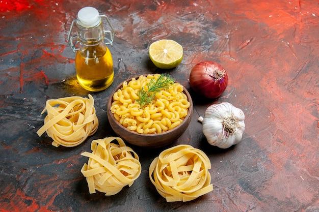 Três macarrões de macarrão e borboleta crus em uma tigela marrom e cebola verde limão frasco de óleo de alho e limão em um fundo de cor mista