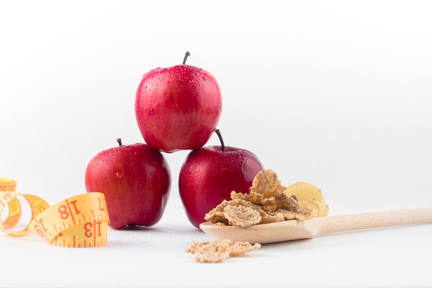 Três maçãs com fita métrica e cereais