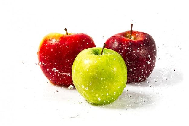 Três maçãs com respingos de água. três maçãs vermelhas, verdes e amarelas com salpicos de warer