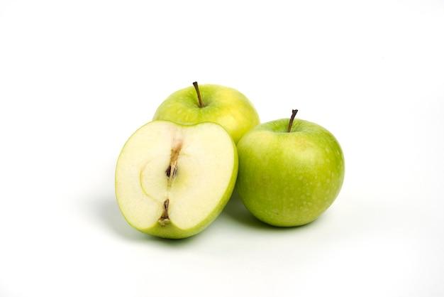 Três maçãs frescas inteiras e fatiadas em fundo branco.