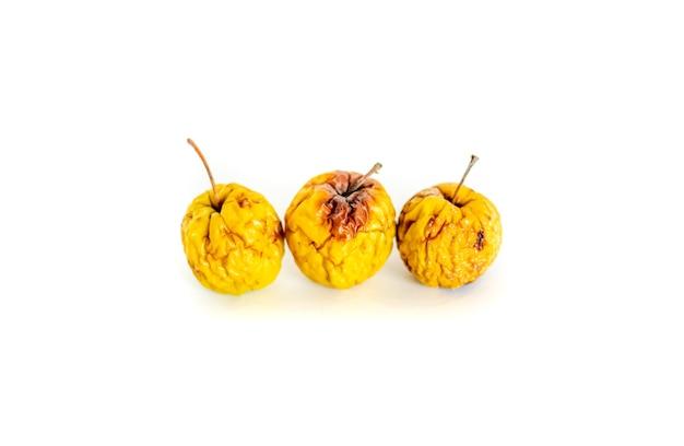 Três maçãs podres estragadas em um fundo branco maçãs podres amarelas em um fundo branco