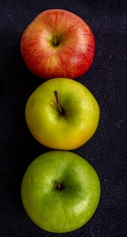 Três maçãs, uma verde e duas vermelhas e amarelas em uma escura.