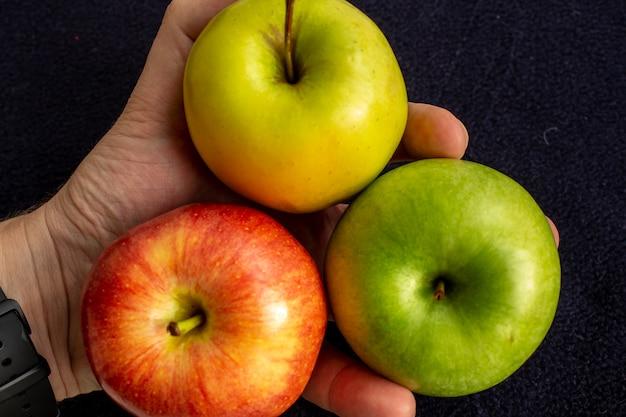 Três maçãs, uma verde e duas vermelhas e amarelas na mão.