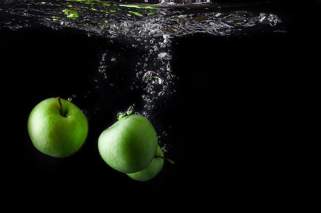 Três maçãs verdes espirrando na água em fundo preto. copie o espaço