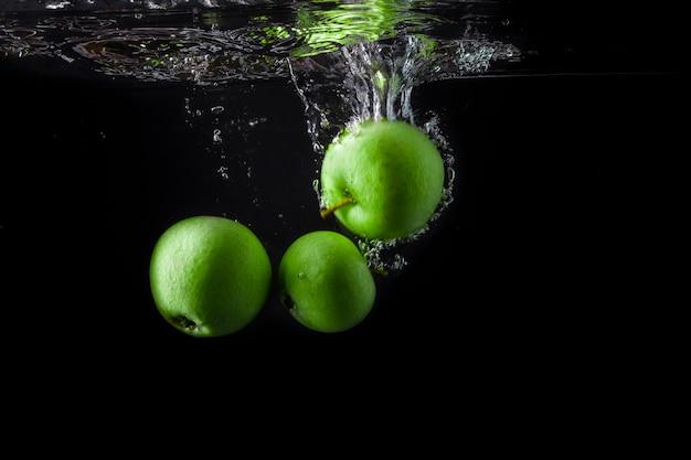 Três maçãs verdes espirrando na água