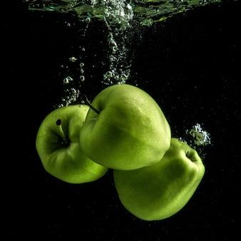 Três maçãs verdes frescas na água
