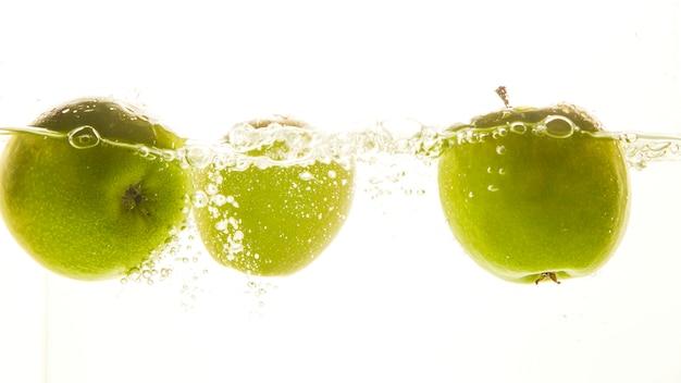 Três maçãs verdes na água.