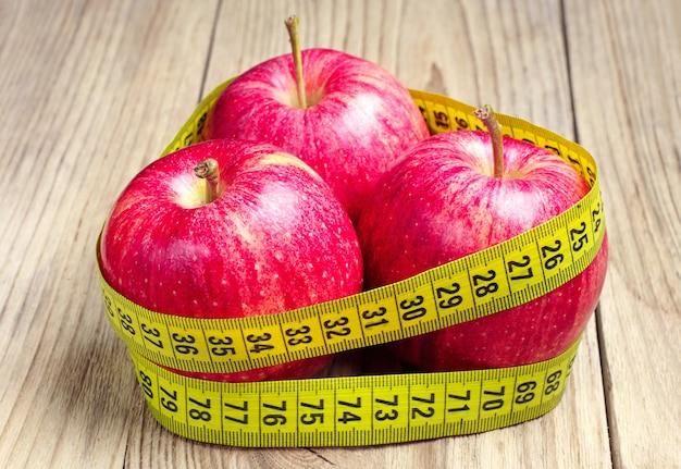Três maçãs vermelhas com fita métrica na mesa de madeira