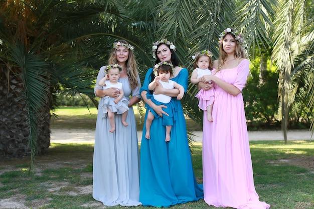 Três mães em lindos vestidos idênticos no parque com bebês. mães amigáveis