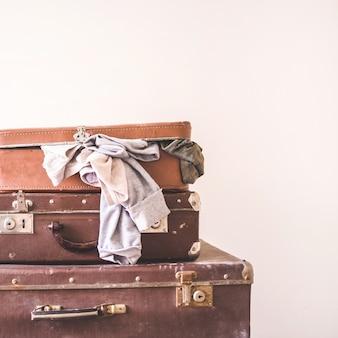 Três malas velhas do vintage com roupas em um fundo claro da parede. estilo retrô rústico